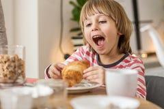 Jonge jongen die croissant eten stock foto