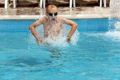 Jonge jongen die in de pool op vakantie springen Stock Afbeelding