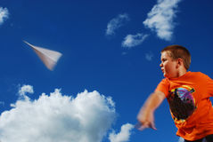 Jonge jongen die document vliegtuig werpt royalty-vrije stock foto's