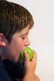 Jonge jongen die een appel eet stock foto's