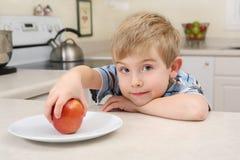 Jonge jongen die een appel voor een snack krijgt stock afbeelding