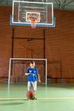 Jonge jongen die een basketbal stuiteren Stock Foto's