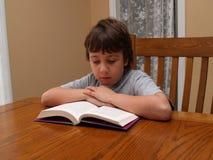 Jonge jongen die een boek leest Stock Foto's