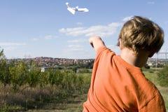 Jonge jongen die een document vliegtuig vliegt stock foto's