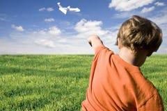 Jonge jongen die een document vliegtuig vliegt royalty-vrije stock afbeelding