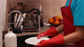 Jonge jongen die een plaat wassen bij de keukengootsteen stock video