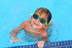 Jonge jongen die in een pool zwemt stock afbeelding