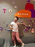 Jonge jongen die gelukkig aan LEGO brocks op de muur richten stock foto