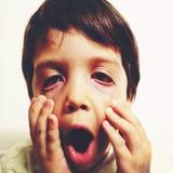 Jonge jongen die gezichten maken Stock Foto's