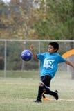 Jonge jongen die goalie met een grote schop speelt Stock Afbeelding