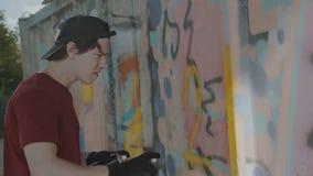 Jonge jongen die in het geheim kleurrijke graffiti trekken op straatmuur 4K stock video