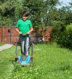 Jonge jongen die het gras met een grasmaaimachine snijden Royalty-vrije Stock Foto's