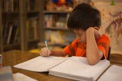 Jonge jongen die het schoolwerk doet Stock Foto