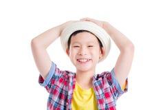 Jonge jongen die hoed en glimlachen over wit dragen stock afbeelding