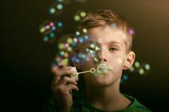Jonge jongen die iriserende bellen blazen Stock Foto's