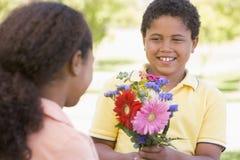 Jonge jongen die jonge meisjesbloemen geeft Stock Foto