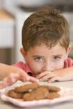 Jonge jongen die in keuken koekjes eet Stock Afbeeldingen