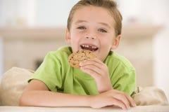 Jonge jongen die koekje in woonkamer het glimlachen eet royalty-vrije stock foto's