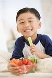 Jonge jongen die kom van groenten in woonkamer eet stock afbeeldingen