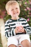 Jonge Jongen die Laarzen met Milkshake draagt Stock Afbeelding