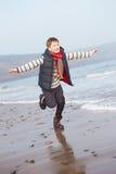 Jonge Jongen die langs de Winterstrand lopen royalty-vrije stock fotografie
