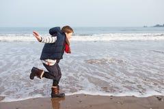 Jonge Jongen die langs de Winterstrand lopen stock fotografie