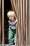 Jonge jongen die met blond of blonde haar en blauwe ogen uit van achter gordijn kijken Royalty-vrije Stock Foto's