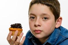 Jonge jongen die met denimoverhemd chocolade cupcake, op wit geïsoleerde achtergrond eten Sluit omhoog portret Royalty-vrije Stock Fotografie