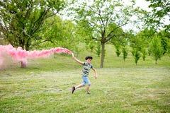 Jonge jongen die met een roze gloed lopen royalty-vrije stock foto