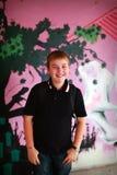 Jonge jongen die met schouderzak agaisnt lacht purpl Royalty-vrije Stock Afbeelding