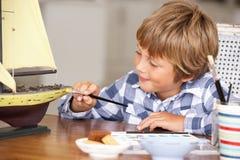 Jonge jongen die modelschip maakt Stock Afbeeldingen
