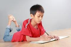 Jonge jongen die op de vloer schrijven Stock Afbeeldingen