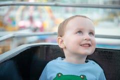 Jonge jongen die op het wiel van de ritferris van het promenadevermaak omhoog kijken Stock Afbeeldingen