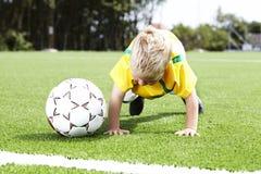 Jonge jongen die opdrukoefeningen op een voetbalgebied doen Royalty-vrije Stock Foto