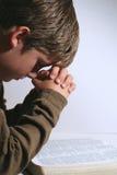 Jonge jongen die over zijn bijbel bidt stock foto