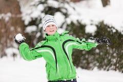 Jonge jongen die sneeuwballen werpen Stock Foto