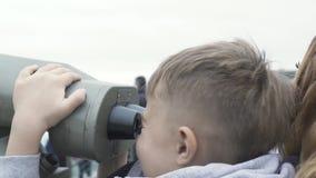 Jonge jongen die stadspanorama door toeristenverrekijkers kijken op Victoria Peak Hong Kong China De moeder van de toeristenjonge stock videobeelden