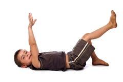 Jonge jongen die ter plaatse zich uitrekt ligt Stock Foto's