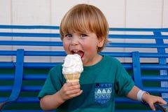 Jonge jongen die terwijl het likken van een roomijskegel glimlachen Stock Foto
