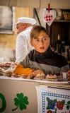 Jonge jongen die traditioneel voedsel op een stadsfestiviteiten voorstellen royalty-vrije stock afbeeldingen