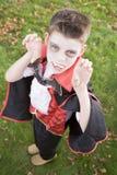 Jonge jongen die vampierkostuum op Halloween draagt stock afbeelding