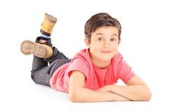 Jonge jongen die in vrijetijdskleding op de vloer leggen stock foto