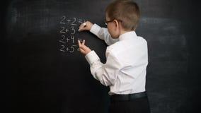 Jonge jongen die wiskundeuitdrukking op een bord oplossen Creatief concept van terug naar school en studie Preschool stock videobeelden
