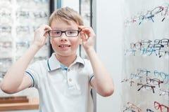 Jonge jongen die zeer gelukkig met zijn nieuwe oogglazen in de opslag zijn stock foto