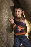 Jonge jongen die zich naast boomboomstam bevinden Stock Foto's