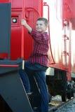 Jonge jongen die zich op een caboose bevinden Stock Foto