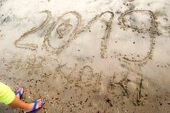 Jonge jongen die zich voor nummer 2019 bevinden geschreven op het overzeese zand met getrokken hart in aantal 0 en tekst Halkidik stock foto's