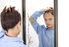 Jonge Jongen die Zijn Haar in Spiegel kammen Royalty-vrije Stock Afbeelding