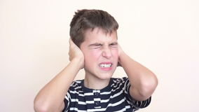 Jonge jongen die zijn oren behandelen stock videobeelden