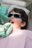 Jonge jongen die zijn tanden heeft die bij de tandarts worden opgepoetst Stock Afbeelding